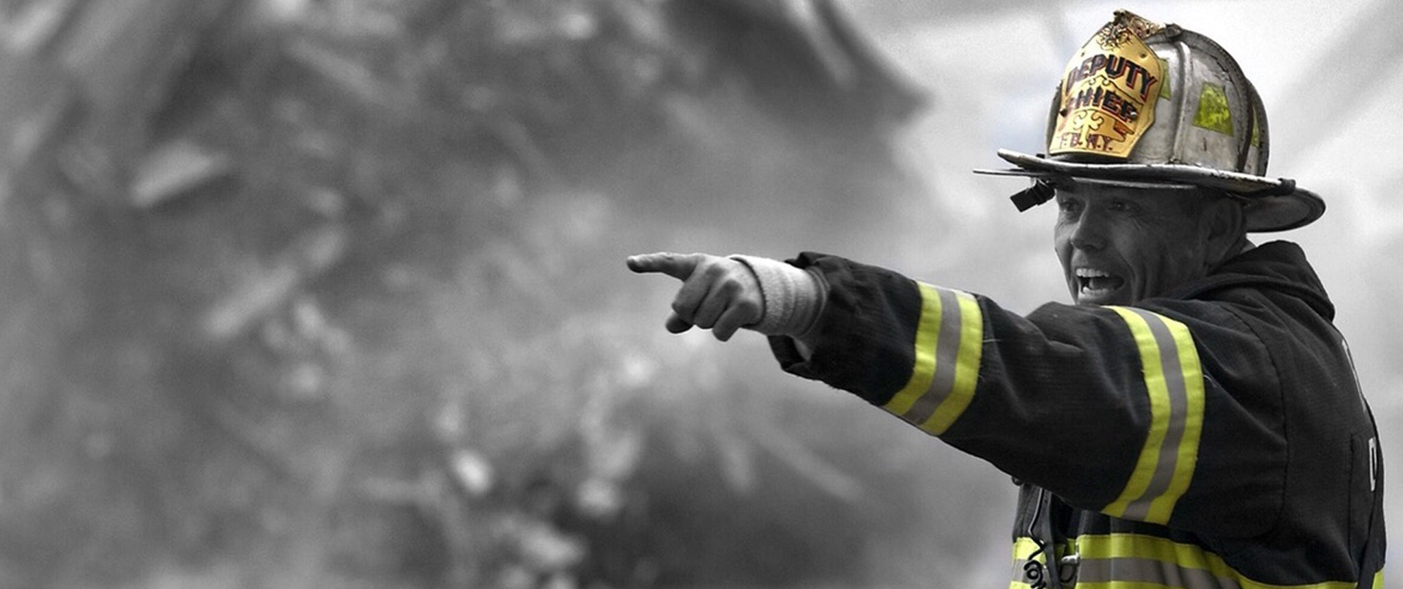 Firefighter pointing to the left in a smoky environment