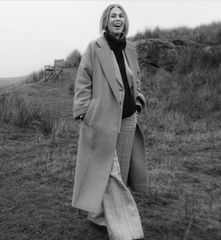 Foxologist Tracy Clayton walking the beach in a lambswool Ryton Roll Neck jumper