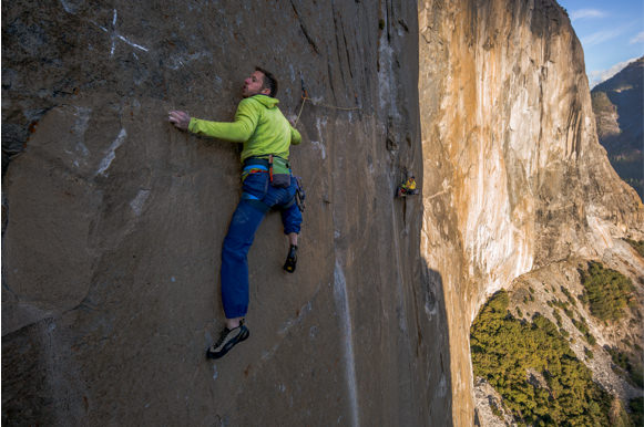 Caldwell climbing the Dawn  Wall during the day. The sun drenches the side of the mountain in warm, orange tones.