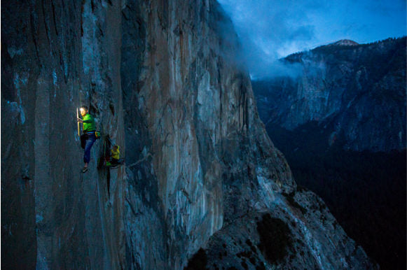 Caldwell climbing the Dawn Wall at night. The side of the mountain takes on a deep blue hue.