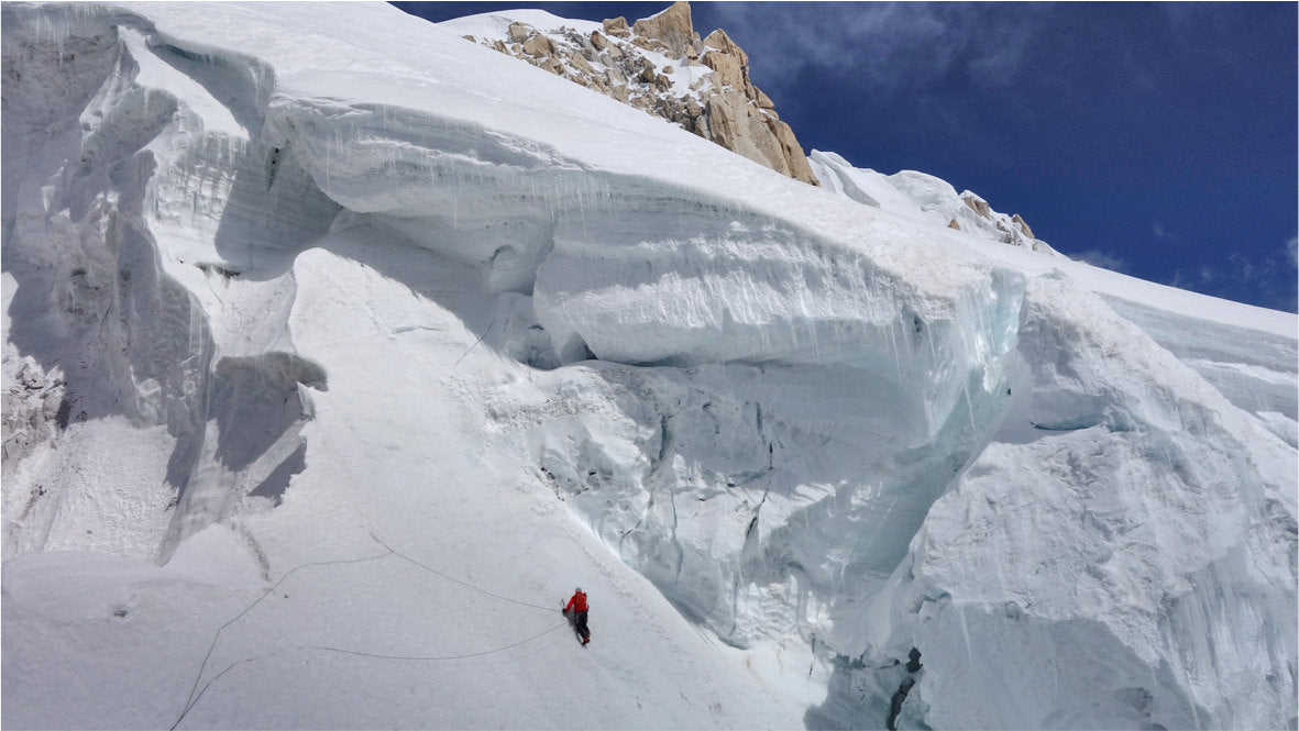 A large, icy mountain. The climber, wearing a bright R1® jacket, is but a speck of orange against the snowy expanse.