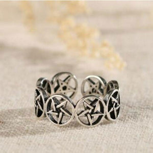 Adjustable Pentagram Ring. A silver band made of lots of small pentagrams, on a light background. It looks very cult-like and mysterious