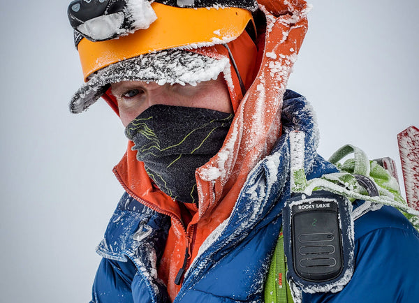 A mountaineer with a blue jacket, orange helmet, and Rocky Talkie squints through the rime ice covering him.