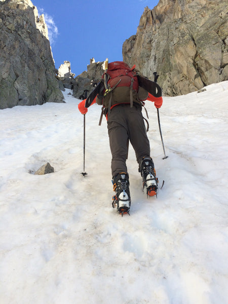 A man hikes uphill through steep snow with skis strapped to his back