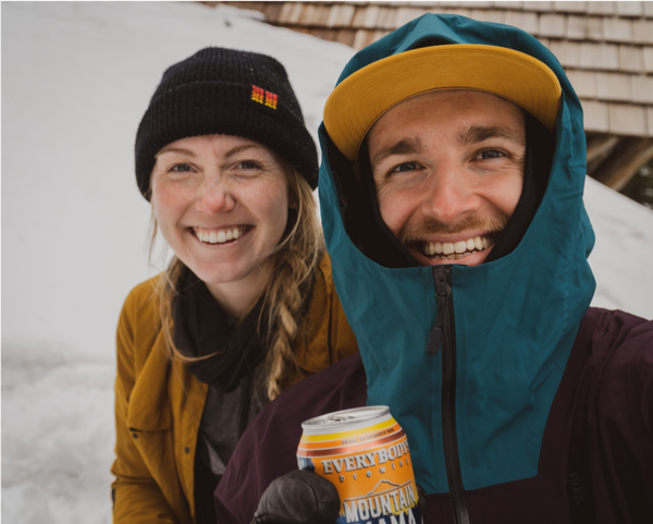 two backcountry skiers share a beer on a snowy summit