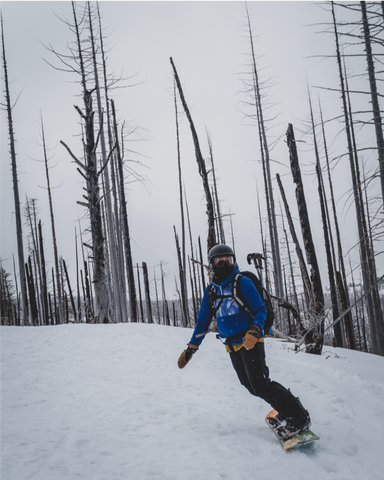 a backcountry splitboarder makes turns through trees