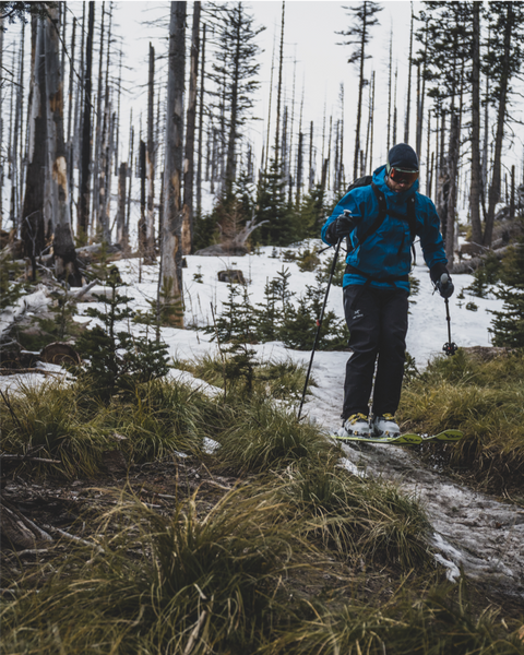 a backcountry skier skis a thin strip of snow on a muddy trail
