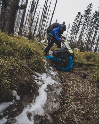 two backcountry skiers help one another stand in the mud