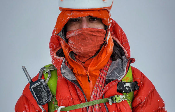 A mountaineer with a red jacket, green backpack, and Rocky Talkie is covered with frost and snow.