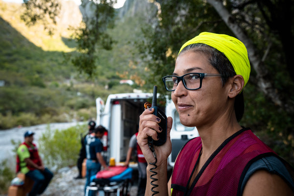 A woman stands near an ambulance, using a Rocky Talkie handheld radio to communicate with rescuers.