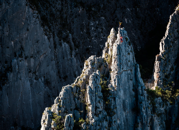Two rock climbers stand atop a limestone fin in El Portero Chico Park, Mexico, in the morning sun.