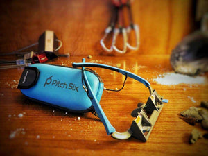 EyeSend belay glasses with case on a wooden background. Quickdraws, nuts and climbing chalk in the background of the belay glasses.