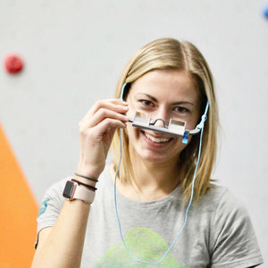 Girl wearing EyeSend Belay Glasses inside of the climbing gym.