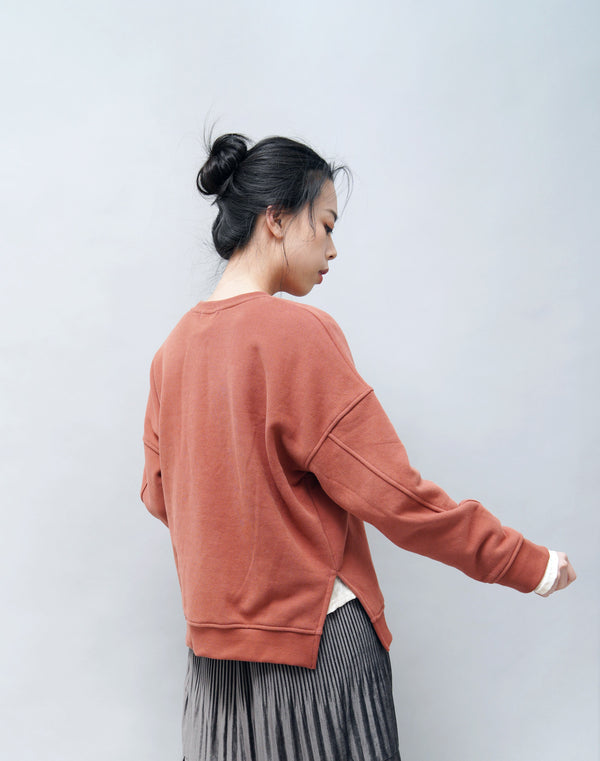Brick red pullover in side vents