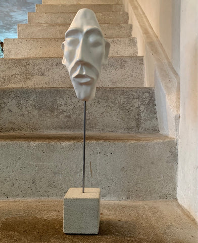 clay face sculpture on  concrete plinth