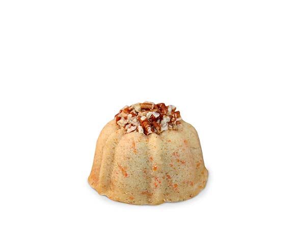 Carrot and cinnamon pound cake in the shape of a bundt filled with cinnamon cream cheese buttercream and topped with toasted pecans. serves 1-2. Each Janie's Cake Petite size pound cake is packaged in a clear container with a Janie's logo sticker and yellow and white striped closure sticker.