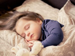 little girl sleeping with stuffed bunny