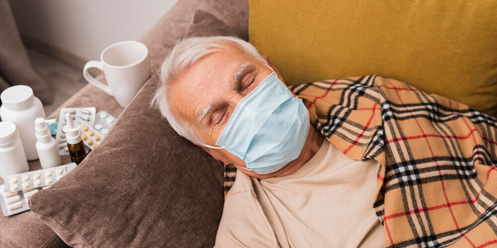 Man sleeping on couch with medical mask