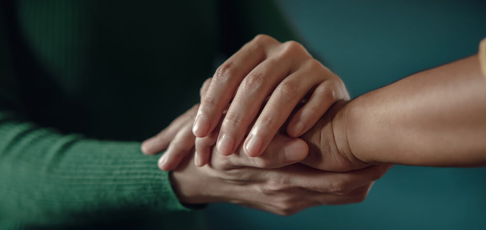two people holding hands in support