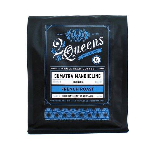 Black bag of coffee beans with blue and white texts that reads Queens