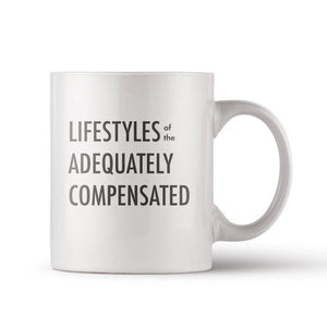 "A white mug with black text: ""LIFESTYLES OF THE ADEQUATELY COMPENSATED."""