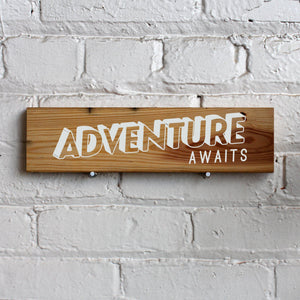 "Square wooden wall sign painted in white the words, ""ADVENTURE awaits!"""