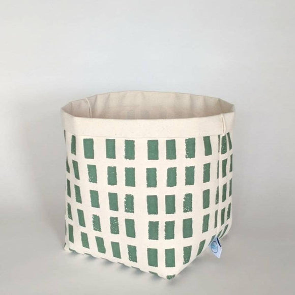 a cream colored canvas bin with green square patterns