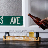 "Wooden beer flights with two black leather holders on the sides. Has text in white that reads ""ARRIVALS DETROIT"""