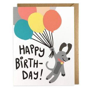 "A white card with text ""HAPPY BIRTHDAY!"" and an image of a cartoon grey dog holding colorful balloons."