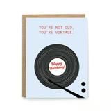 "Light blue card with red text: ""YOU'RE NOT OLD, YOU'RE VINTAGE. HAPPY BIRTHDAY!"" with an image of a black record player. Comes with brown envelope."