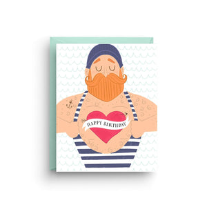 "A white card with an illustration of a ginger headed sailor man showing his heart that reads ""HAPPY BIRTHDAY!"" Comes with a light blue envelope."