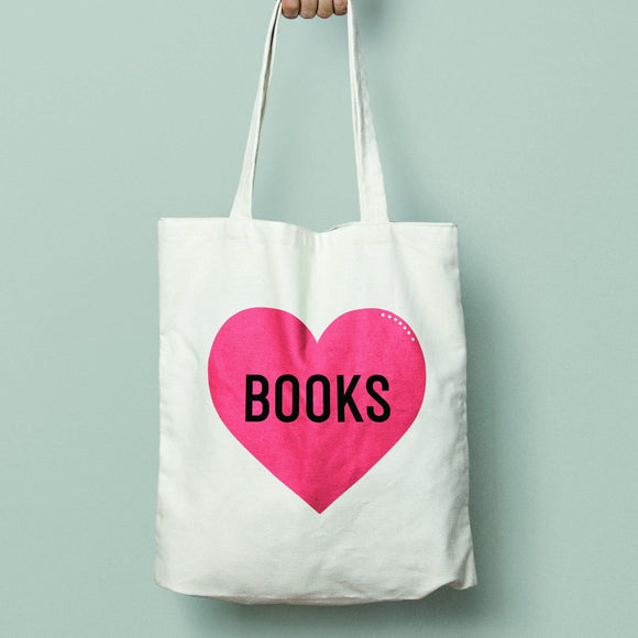 A canvas tote bag with a red heart in the center has a black text: