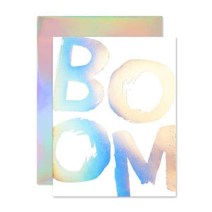 "A white card with a holographic text: ""BOOM."""