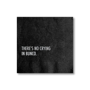 "A black napkin with a white text: ""THERE'S NO CRYING IN BUNCO."""