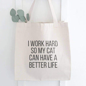 "A white canvas tote with a black text: ""I WORK HARD SO MY CAT CAN HAVE A BETTER LIFE."""