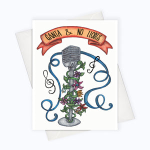 "A white card with a black text: ""CANTA & NO LLORES"" and an illustration of a mic and flowers. Comes with a white envelope."