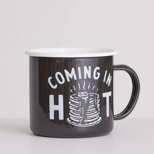 "A black mug with a white text: ""COMING IN HOT"" and an illustration of panckaes."