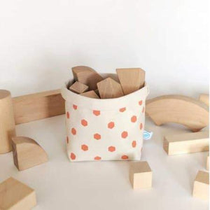 A beige canvas bin with coral colored hexagon patterns.