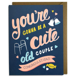 "A navy colored card with pink text: ""YOU'RE GONNA BE A CUTE OLD COUPLE. CONGRATULATIONS!"" Comes with a brown envelope."