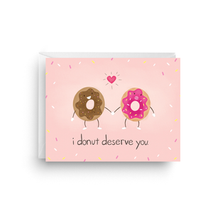 "A pink card with a text: ""I DONOT DESERVE YOU"" and an illustration of two donuts holding hands. Comes with a white envelope."
