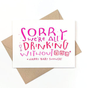 "A white card with a pink text: ""SORRY WE'RE ALL DRINKING WITHOUT YOU. HAPPY BABY SHOWER!"" Comes with a brown envelope."