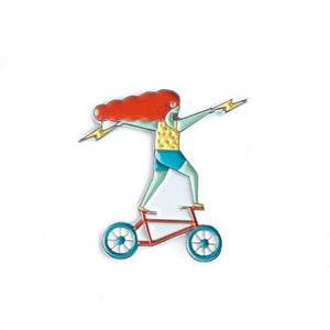 An enamel pin of a red hair girl standing on a bicycle.