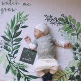 "A baby on a blanket with a watercolor illustration of foliage and a caligraphy text: ""WATCH ME GROW."""