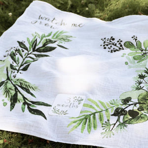 "A white blanket with a watercolor illustration of a foliage and a caligraphy text: ""WATCH ME GROW."""