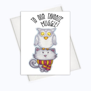 "A white card with a black text: ""TO OUT FAVORITE MUGGLE"" and an illustration of an owl and a cat wearing the Harry Potter scarf. Comes with a white envelope."