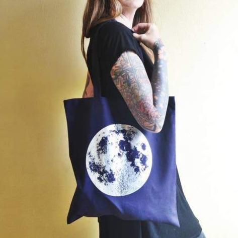 A navy blue tote bag with an illustration of a moon.
