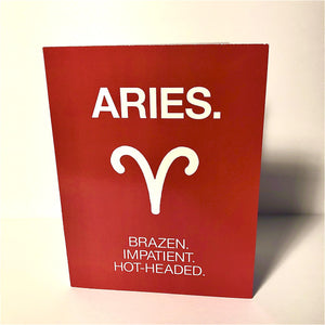"A red card with a white text: ""ARIES. BRAZEN, IMPATIENT, HOT-HEADED"" and an illustration of the Aries sign symbol"