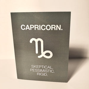 "A dark grey card with a white text: ""CAPRICORN. SKEPTICAL, PESSIMISTIC, RIGID"" and an illustration of the Capricorn sign symbol."