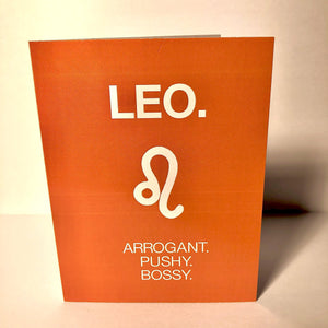 "An orange card with a white text: ""LEO. ARROGANT, PUSHY, BOSSY"" and an illustration of the Leo sign symbol."