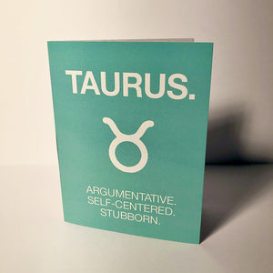 "A teal colored card with a white text: ""TAURUS> ARGUMENTATIVE, SELF- CENTERED, STUBBORN"" and an illustration of the Taurus sign symbol."